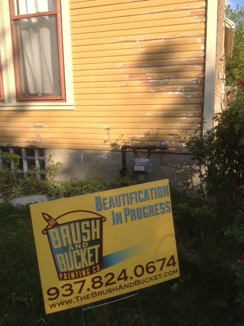 The Brush and Bucket- sign with a house getting a proper prep job