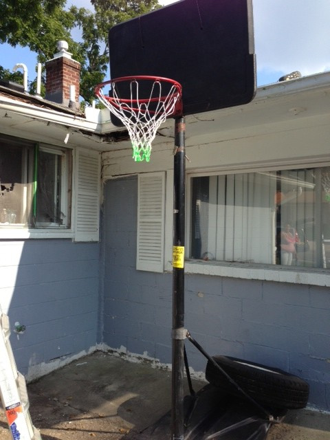 David Esrati hangs basketball nets as part of his election campaign.