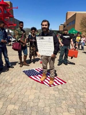 Photo of a protester at Wright State University standing on the American Flag