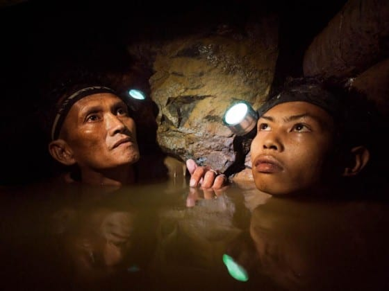 An older miner and a younger boy are chin deep in frigid water 150-meters below the surface as they work a gold mine near Syndicate on the island of Masbate. Image by Larry C. Price. Philippines, 2012.